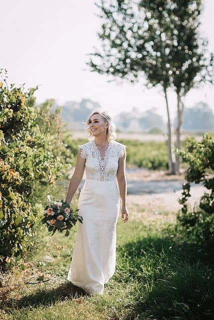 bride walking through the vines in swan valley