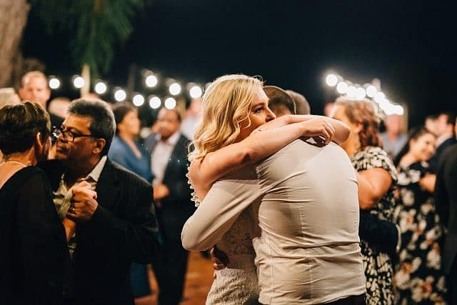 While dancing a bride and groom lovingly hug each other