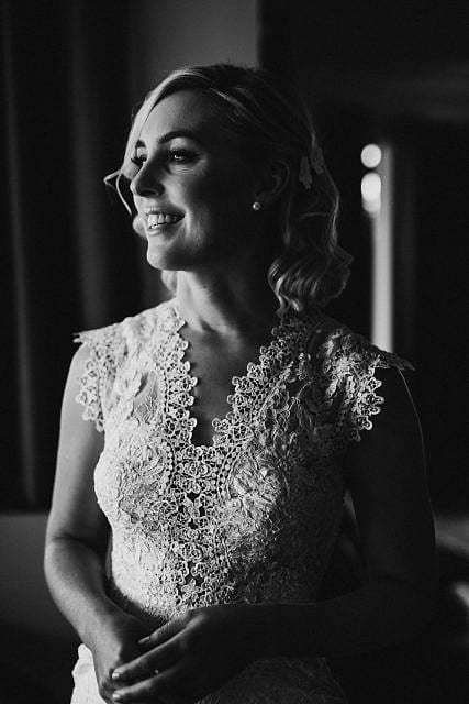 Bride smiles elegantly for a picture before going to ceremony