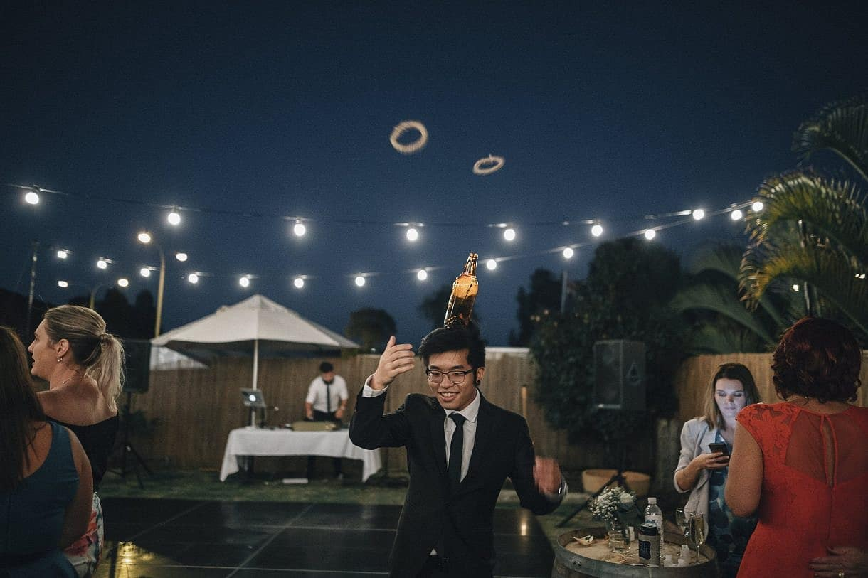 Guests play with games in the DIY backyard Perth property wedding