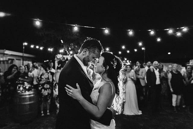 Wedding couple dance under lights and with family & friends glowingly supporting them in the background