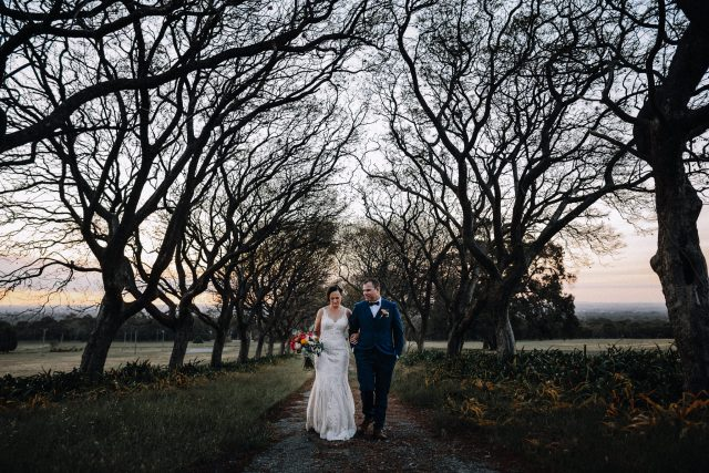 Bride & Groom walking through the trees at Quarry Farm Wedding